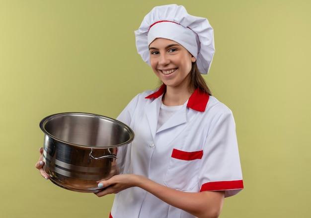 Jovem sorridente caucasiana cozinheira com uniforme de chef segurando a panela e olhando para a câmera isolada em um fundo verde com espaço de cópia