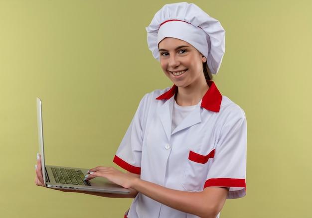 Jovem sorridente caucasiana cozinheira com uniforme de chef segurando laptop em verde com espaço de cópia
