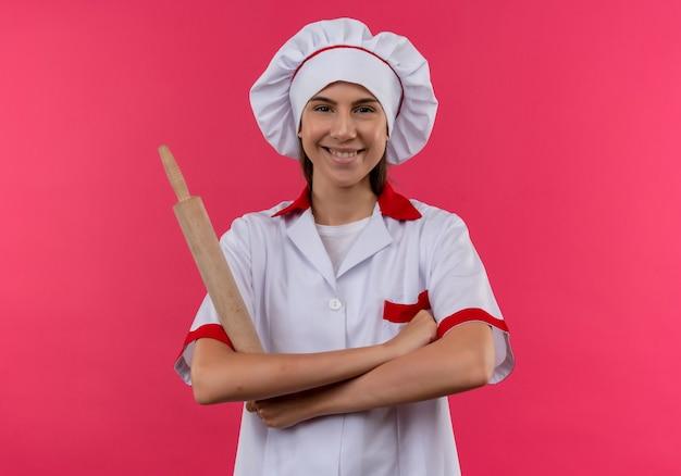 Jovem sorridente caucasiana cozinheira com uniforme de chef segurando o rolo com os braços cruzados, isolado no espaço rosa com espaço de cópia