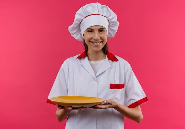 Jovem sorridente caucasiana cozinheira com uniforme de chef segurando um prato isolado no espaço rosa com espaço de cópia