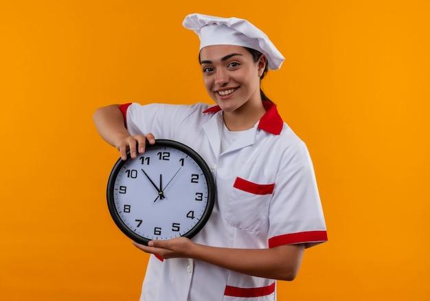 Jovem sorridente caucasiana cozinheira com uniforme de chef segurando um relógio com as duas mãos isoladas na parede laranja