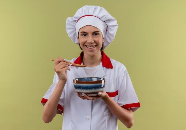 Jovem sorridente caucasiana cozinheira com uniforme de chef segurando uma tigela e uma colher no verde com espaço de cópia
