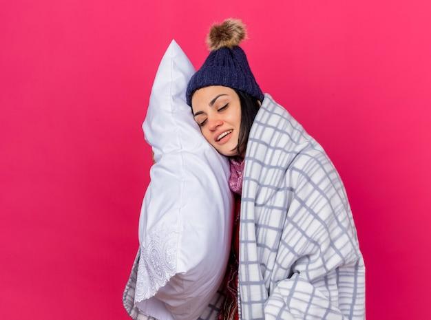 Jovem sorridente caucasiana doente usando chapéu de inverno e lenço enrolado em um travesseiro xadrez, colocando a cabeça nele com os olhos fechados, isolado na parede carmesim com espaço de cópia