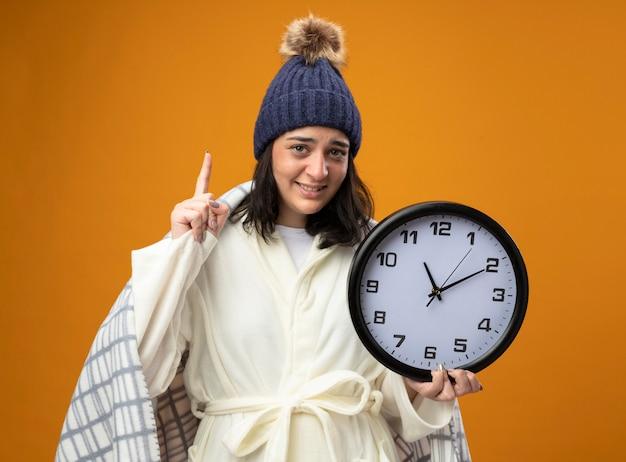 Jovem sorridente caucasiana doente usando um manto de inverno, envolto em uma manta segurando um relógio, olhando para a câmera apontando para cima, isolado em um fundo laranja