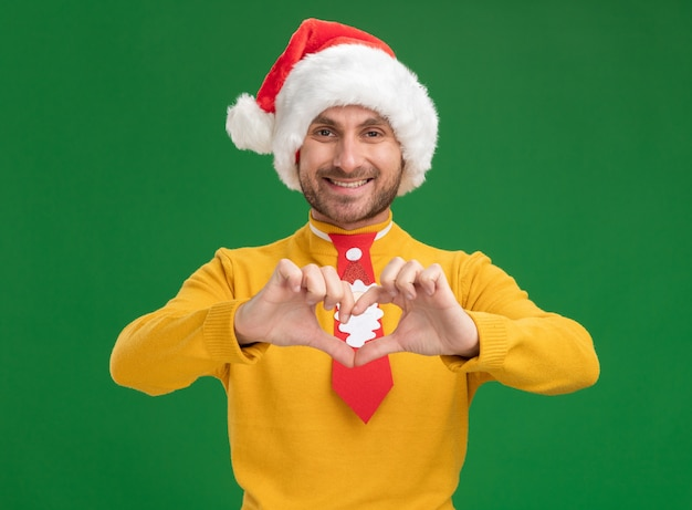 Jovem sorridente, caucasiano, usando chapéu de natal e gravata, olhando para a câmera, fazendo um sinal de coração isolado sobre fundo verde
