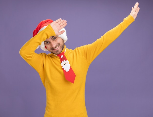 Jovem sorridente, caucasiano, usando um chapéu de natal e gravata, olhando para a câmera, fazendo um gesto levemente isolado no fundo roxo