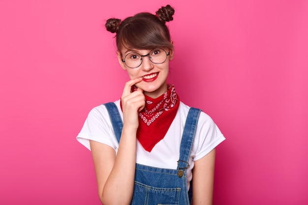 Jovem sorridente colegial linda com longos cabelos chocolate, mantém o dedo indicador nos lábios. o estudante de cabelos escuros volta para a escola e pensa em novos assuntos. garota fica contra a parede rosa.