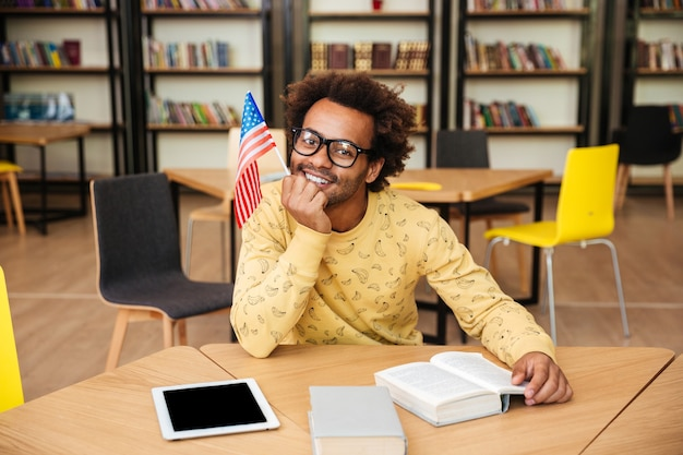 Jovem sorridente com a bandeira sentada e lendo um livro na biblioteca