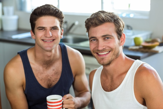 Jovem sorridente com amigo segurando a xícara de café em casa