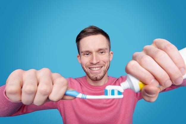 Jovem sorridente com barba segurando a escova de dentes e aplicando pasta de dente
