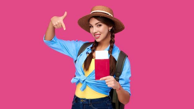Jovem sorridente com carteira de identidade ou passaporte segurando a passagem de avião, mostrando o gesto do dedo no fundo rosa brilhante. mulher caucasiana em roupas casuais e chapéu de palha. estudante européia