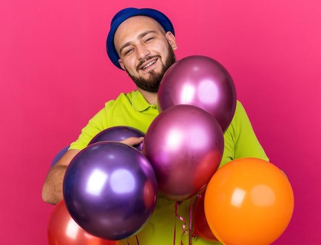 Jovem sorridente com chapéu de festa atrás de balões