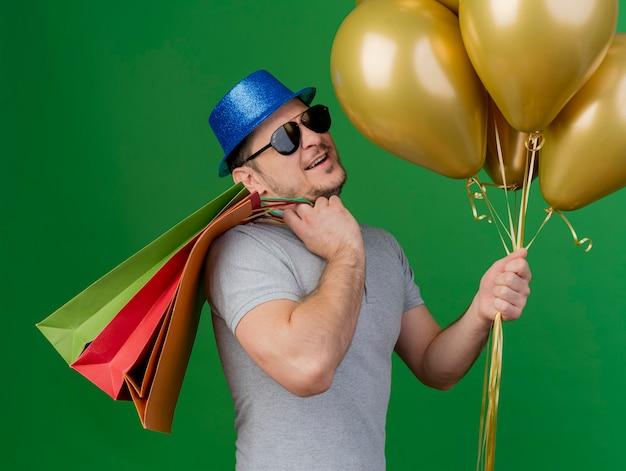 Jovem sorridente com chapéu de festa e óculos, colocando sacolinhas de presente no ombro segurando balões isolados no verde