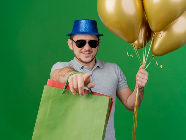 Jovem sorridente com chapéu de festa e óculos, segurando balões com sacolinhas e mostrando um gesto isolado no verde