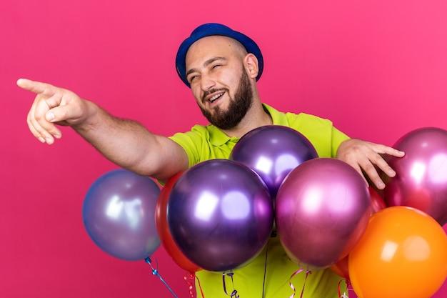 Jovem sorridente com chapéu de festa em pé atrás de balões apontando para o lado isolado na parede rosa