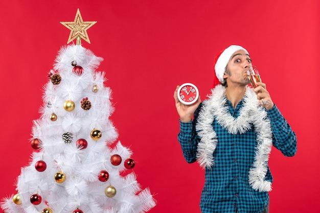 Jovem sorridente com chapéu de papai noel, desfrutando de uma taça de vinho e segurando o relógio em pé perto da árvore de natal no vermelho