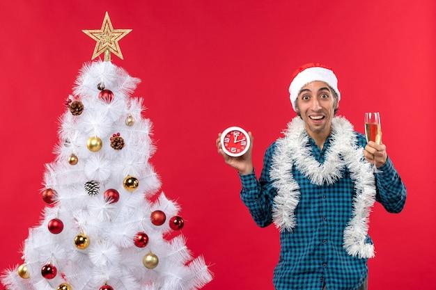Jovem sorridente com chapéu de papai noel e segurando uma taça de vinho e um relógio em pé perto da árvore de natal no vermelho