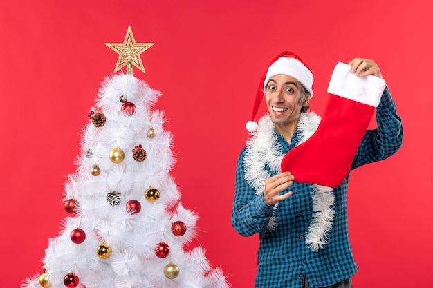 Jovem sorridente com chapéu de papai noel em uma camisa azul listrada e segurando uma meia de natal