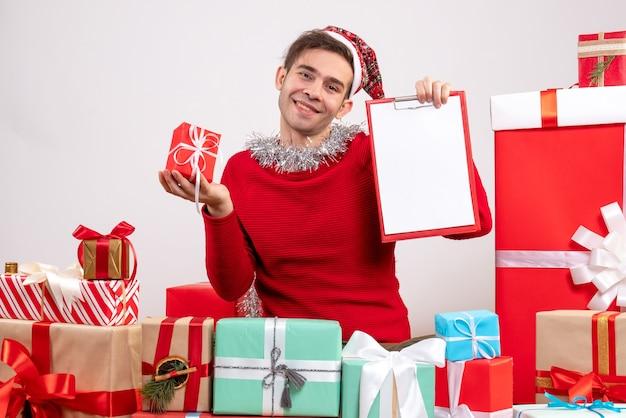 Jovem sorridente com chapéu de papai noel sentado em frente aos presentes de natal
