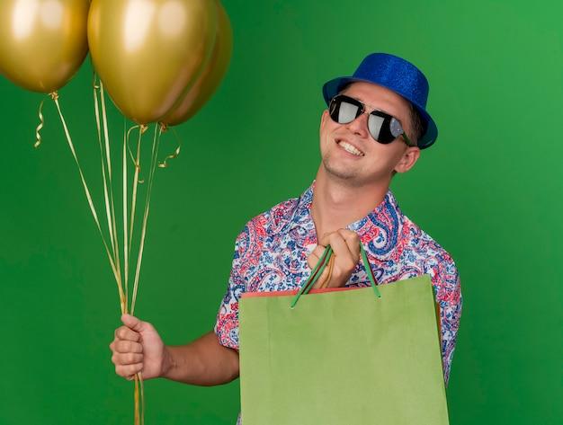 Jovem sorridente com chapéu e óculos azuis, segurando sacolas de presente com balões isolados no verde