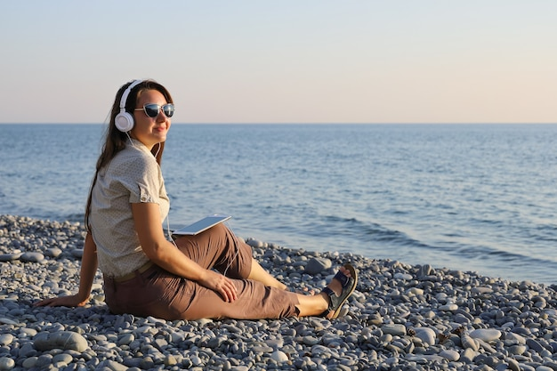 Jovem sorridente com fones de ouvido brancos e óculos escuros ouvindo música na praia de seixos