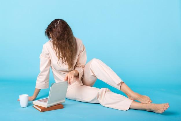 Jovem sorridente com pijama em casa, posando com livros, enquanto descansa em casa