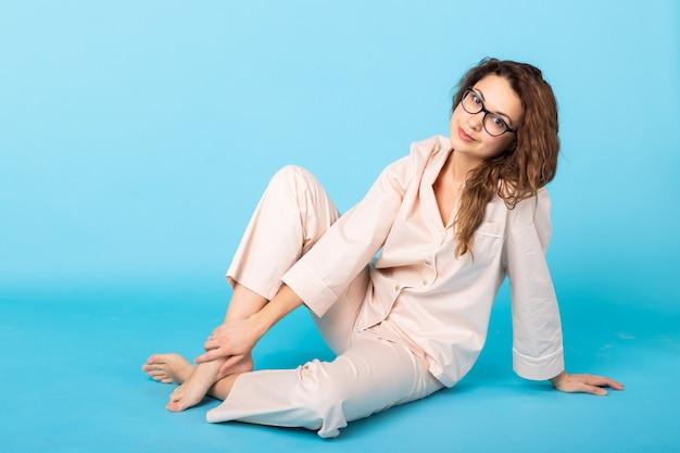 Jovem sorridente com pijama em casa, posando enquanto descansava em casa, isolada na parede azul