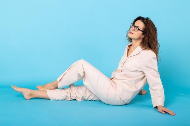 Jovem sorridente com pijama em casa, posando enquanto descansava em casa, isolada sobre fundo azul