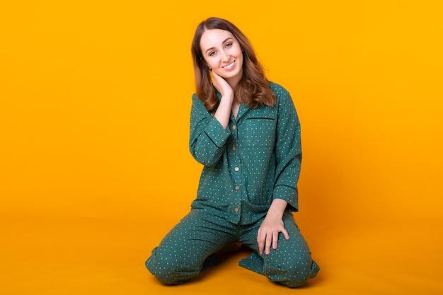 Jovem sorridente com pijama em casa, usar posando enquanto descansava em casa, isolada na parede amarela