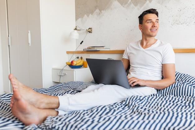 Jovem sorridente com roupa de pijama casual sentado na cama de manhã trabalhando em um laptop