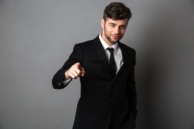 Jovem sorridente com roupa formal, apontando com o dedo em você,