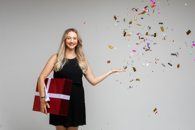 Jovem sorridente com um grande presente festivo apontando com a mão em um espaço vazio com confetes de férias em fundo cinza