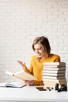 Jovem sorridente com um suéter amarelo lendo um livro e rindo