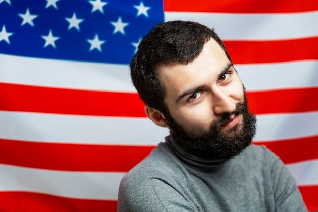 Jovem sorridente com uma barba em um fundo da bandeira americana. fechar-se. dia da independência.