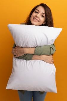 Jovem sorridente com uma camiseta verde oliva abraçada com um travesseiro isolado na parede amarela
