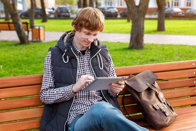 Jovem sorridente com uma mochila no parque lendo uma redes sociais via tablet