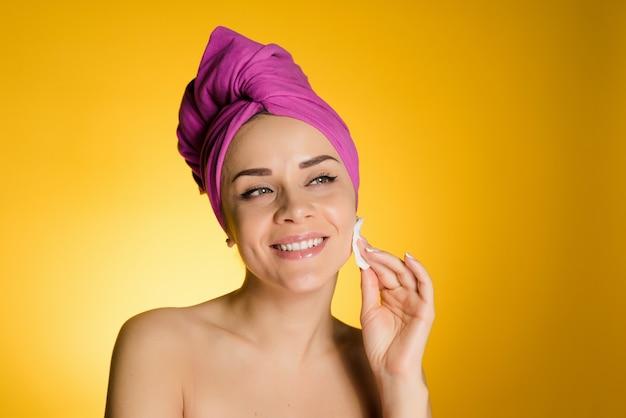 Jovem sorridente com uma toalha rosa na cabeça limpa a pele com uma bola de algodão