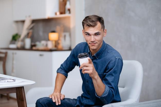 Jovem sorridente com uma xícara de café apontando para você