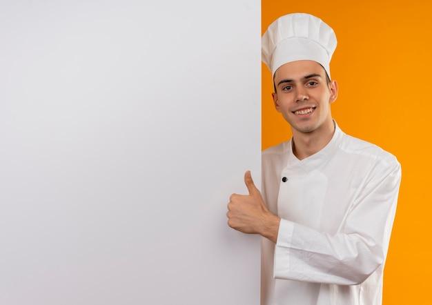 Jovem sorridente com uniforme de chef e segurando uma parede branca com o polegar para cima