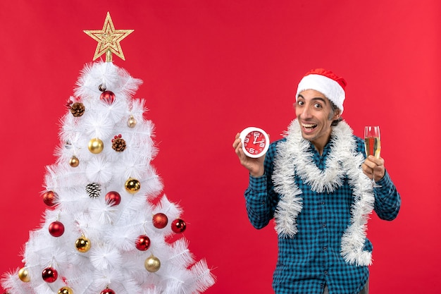 Jovem sorridente confiante com chapéu de papai noel, segurando uma taça de vinho e um relógio perto da árvore de natal