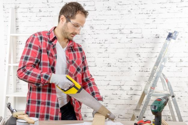 Jovem sorridente cortando uma placa com uma serra de mão