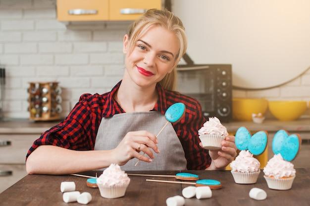 Jovem sorridente cozinhando bolos caseiros na cozinha