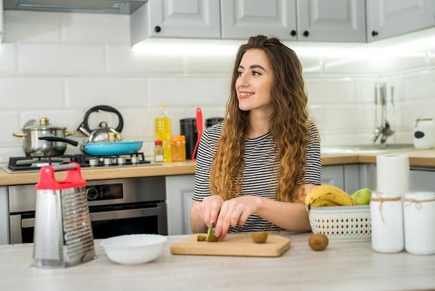 Jovem sorridente cozinhando salada fresca com frutas na cozinha