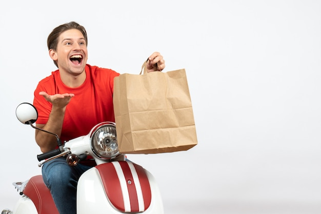 Jovem sorridente curioso mensageiro de uniforme vermelho sentado na scooter segurando um saco de papel na parede branca