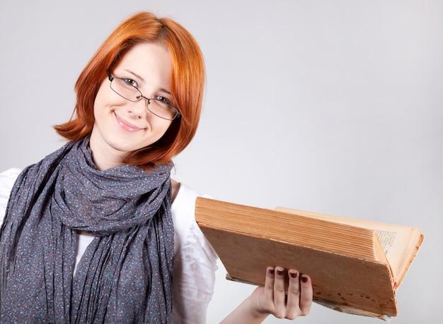 Jovem sorridente da moda de óculos com um livro velho