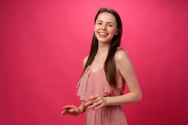 Jovem sorridente dançando com os braços estendidos contra um fundo rosa