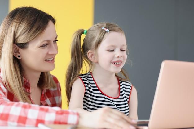 Jovem sorridente dando aulas com a criança no laptop