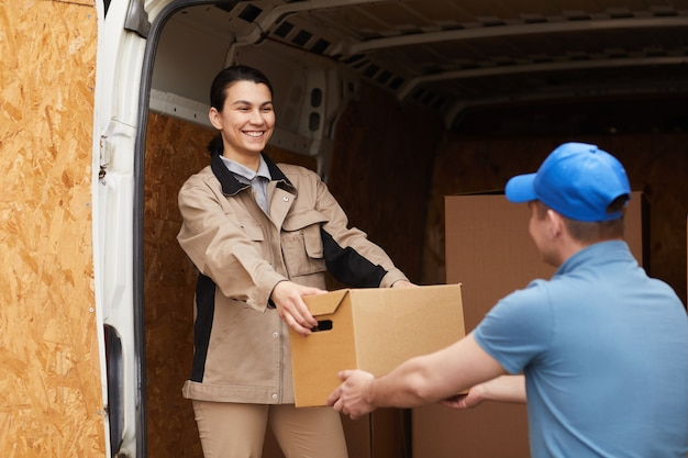 Jovem sorridente dando uma caixa para seu colega e eles descarregando as caixas da van ao ar livre