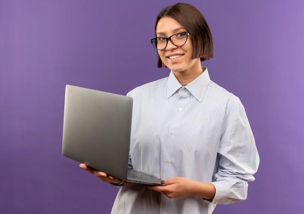 Jovem sorridente de call center usando óculos segurando um laptop isolado na parede roxa
