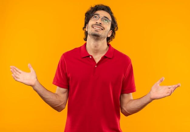Jovem sorridente, de camisa vermelha e óculos ópticos, de mãos abertas, olhando para cima, isolado na parede laranja